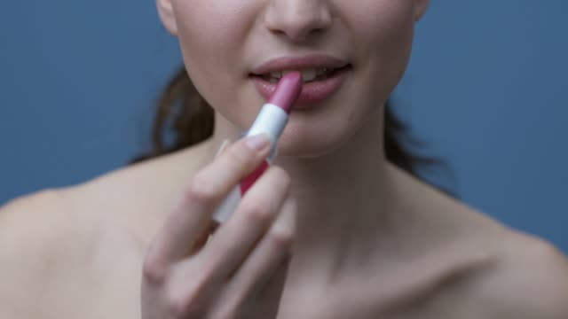 Young woman applying lipstick Young beautiful woman applying a pink lipstick on her lips and smiling lip balm stock videos & royalty-free footage