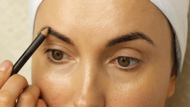 stockvideo's en b-roll-footage met jonge vrouw toepassing van make-up thuis. - eyeliner