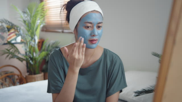 młoda kobieta nakładająca maskę na skórę twarzy. - rozpieszczać się filmów i materiałów b-roll