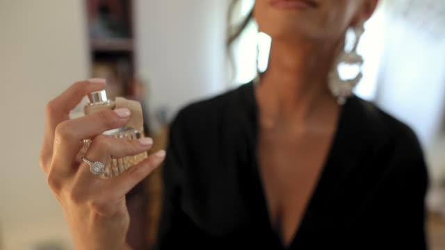 genç kadın uygulama parfüm - kokulu stok videoları ve detay görüntü çekimi
