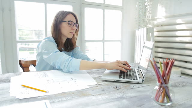 Young woman architect working in her office. Young woman architect working at her sketches and using the laptop in her office. interior designer stock videos & royalty-free footage