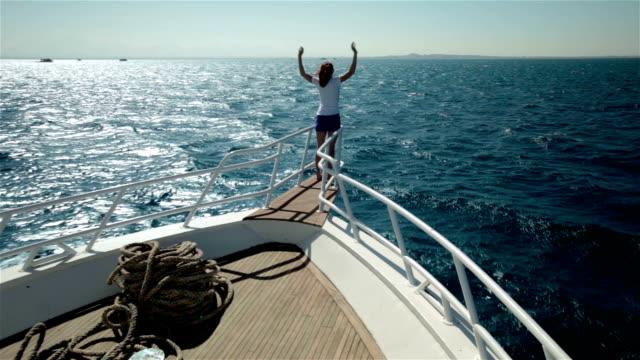 vídeos de stock e filmes b-roll de jovem braços com asas de pássaro no iate barco, a desfrutar do sol prowconstellation name (optional), vida e o nosso mar. sorrir e olhar céu claro - enjoying wealthy life