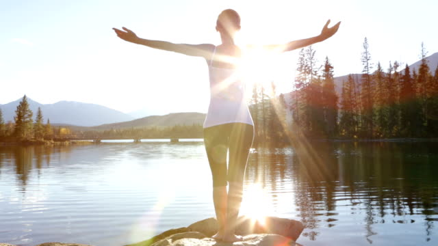 Young woman arms outstretched by the lake Rear view of a young woman practicing yoga by the lake. Sun reflections on the water. healthy lifestyle stock videos & royalty-free footage