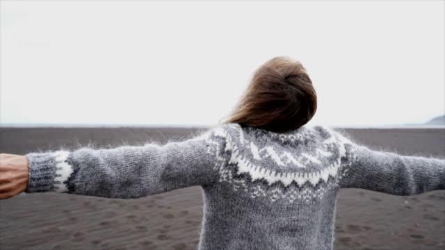young woman arms outstretched by the sea standing on black sand beach, hair in wind- iceland - female running playful enjoying nature and freedom- slow motion - spettinato video stock e b–roll