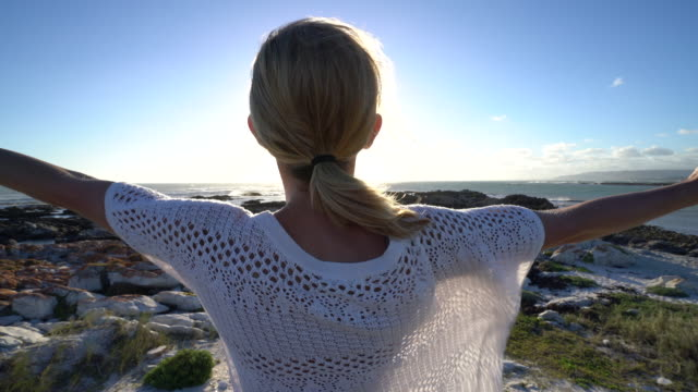 Young woman arms outstretched on beach, relaxation video