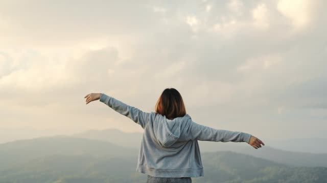 Young woman arms outstretched relaxation and freedom on Top Mountain
