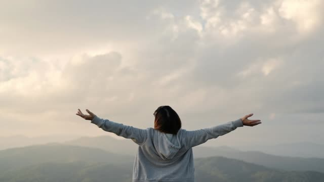 young woman arms outstretched relaxation and freedom on top mountain - in cima video stock e b–roll