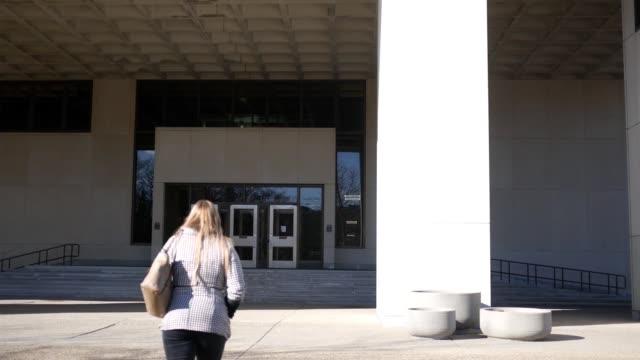 Joven, llegar al trabajo temprano en la mañana en un centro de la ciudad - vídeo