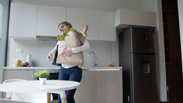 young woman arriving home carrying her groceries leaving keys on table while on a phone call - grocery home video stock e b–roll