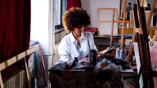 Young woman artist painting in her studio video