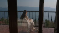 istock Young woman artist working on portrait on verandah above the sea 1255956640