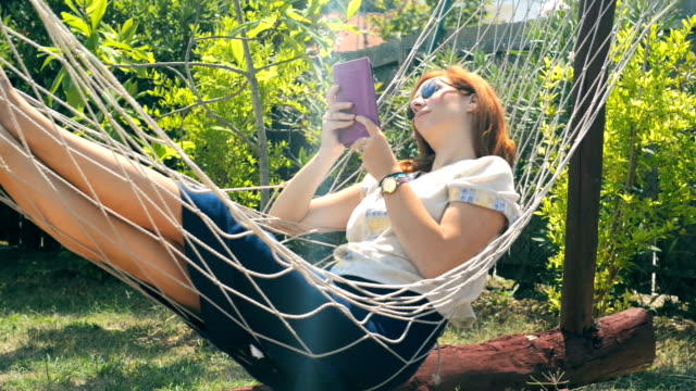 Young woman at 30s relaxing on the hammock II video