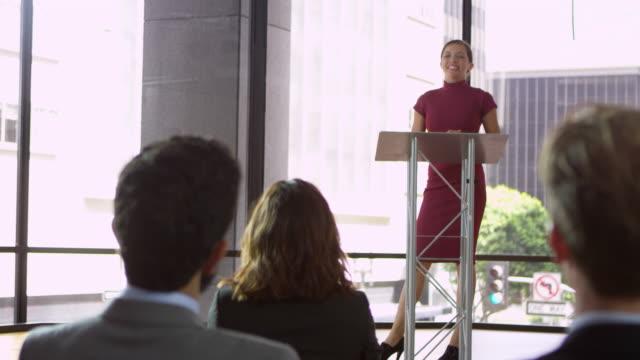 vídeos de stock e filmes b-roll de young woman at a lectern presenting a business seminar, shot on r3d - orador público