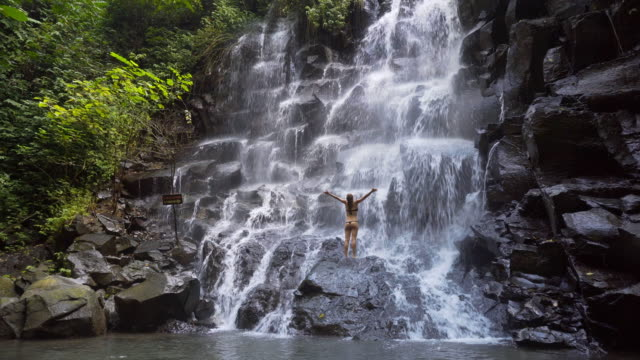 Young woman at a waterfall with her arms outstretched video