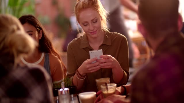 Young woman at cafe with friends, texting on mobile phone
