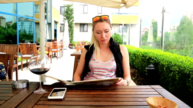 Young Woman at Cafe with menu Young Woman looking for cafe's menu for choosing meal at Cafe menu stock videos & royalty-free footage