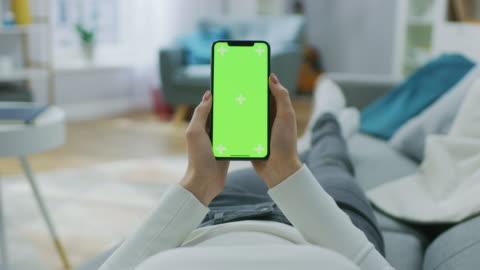 vídeos de stock, filmes e b-roll de mulher jovem em casa deitada em um sofá usando com smartphone de tela verde mock-up. menina usando telefone celular, navegar pela internet, assistir conteúdos, conversando nas redes sociais com amigos. pov. - smartphone