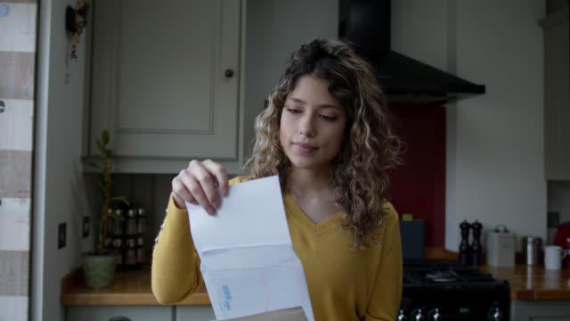 vídeos de stock e filmes b-roll de young woman at home opening her mail - carta documento