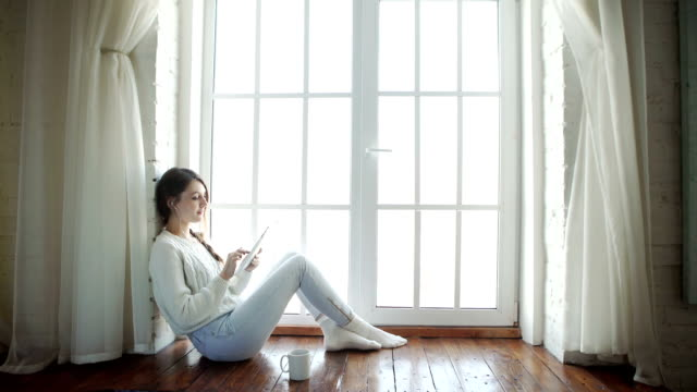 Young woman at home sitting in front of window relaxing using tablet video