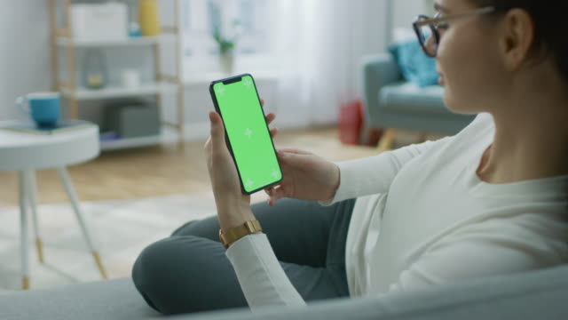 年輕的婦女在家裡使用綠色類比螢幕智慧手機。她坐在他舒適的客廳裡的沙發上肩部相機拍攝 - 模板 個影片檔及 b 捲影像