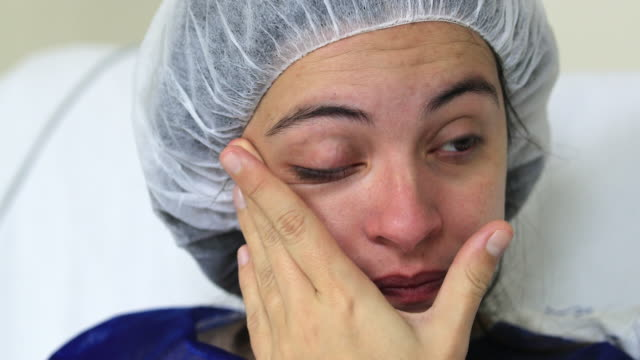Young woman at hospital suffering wiping tears in pain Young woman at hospital suffering wiping tears in pain cancer patient stock videos & royalty-free footage