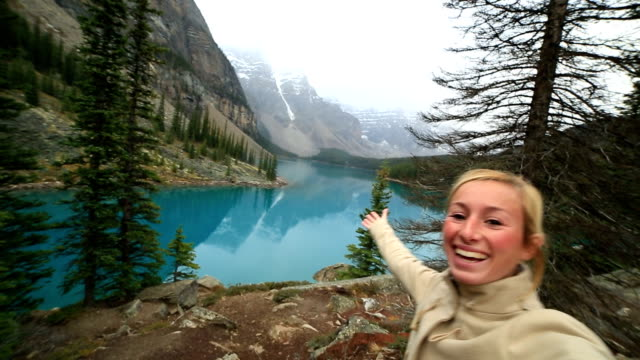 Young woman at Moraine lake taking a selfie portrait video