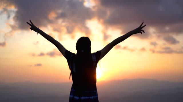 山頂の日没の若い女性はvサインを作る - 希望点の映像素材/bロール