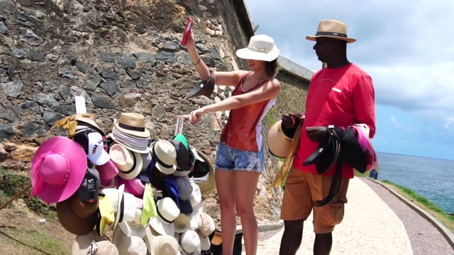 Young woman at street market choosing hat video