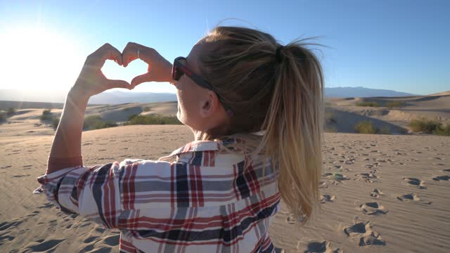 Young woman at sunset on sand dunes making heart shape frame with hands - Love concept.