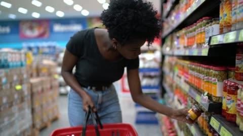 vidéos et rushes de jeune femme à l'étagère de supermarché - faire les courses