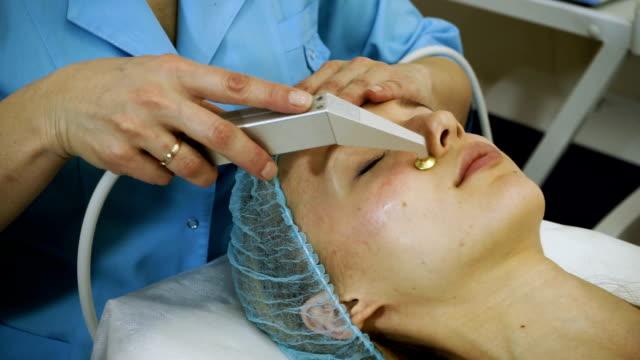 eine junge frau bei der kosmetikerin. das verfahren für eine tiefe hydratation der haut. hd - kosmetische behandlung stock-videos und b-roll-filmmaterial