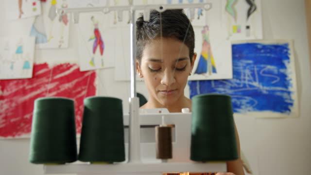 giovane donna al lavoro come sarto nell'atelier di progettazione moda - sarta video stock e b–roll