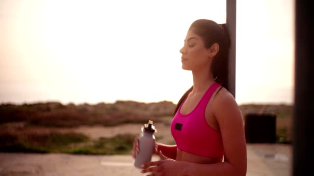 Young woman athlete drinking water after training at sunset Young fit woman drinking an energy drink after outdoors training session at sunset nutritional supplement stock videos & royalty-free footage