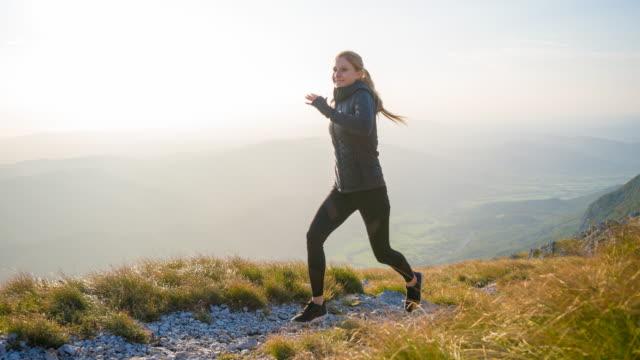 ung kvinna idrottsman kör upp ett berg - jogging hill bildbanksvideor och videomaterial från bakom kulisserna