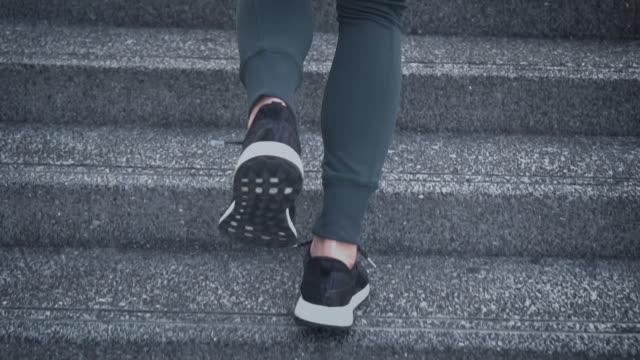 slo mo ung kvinna idrottsman kör upp för trapporna - trappa bildbanksvideor och videomaterial från bakom kulisserna