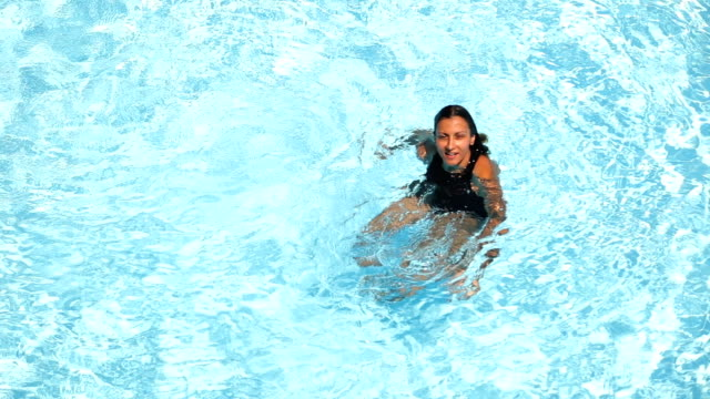 vídeos de stock e filmes b-roll de young woman backstroke swimming in the pool - swim arms