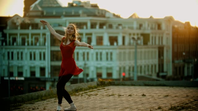 屋根の上で踊る若い女性バレリーナ - 彼女のつま先の上を歩く - バレエ点の映像素材/bロール