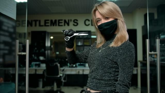 vidéos et rushes de jeune barbier de femme dans le masque protecteur marchant à l'intérieur du salon de coiffure moderne - salons et coiffeurs