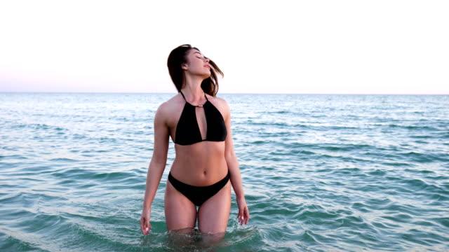 jovem mulher banha no mar, garota Sexy vem para o mar, as férias de verão, gosta de corpo de férias no resort, lindo molhado de mulher - vídeo