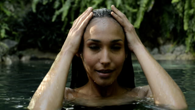 Young woman bathing in a natural pool video