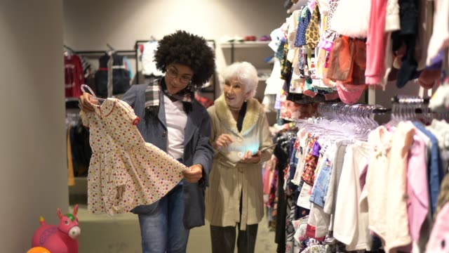 Young woman being helped by a saleswoman while shopping for clothes in a thrift store