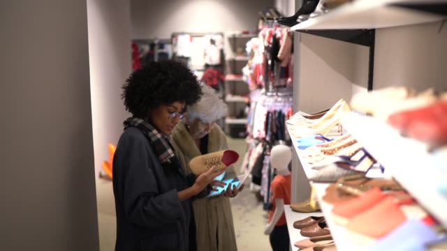 Young woman being helped by a saleswoman while shopping for shoes in a thrift store