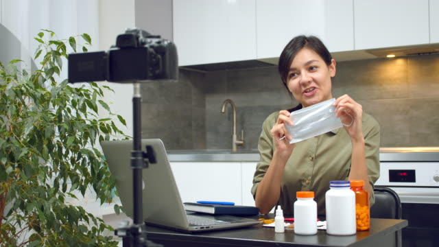 Young woman blogger instructing on proper putting on a medical mask and recording video on camera at home.