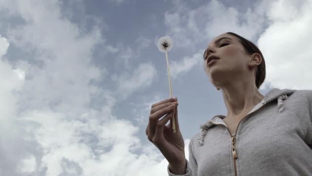 タンポポの花の種を吹く若い女性 - ふわふわ点の映像素材/bロール