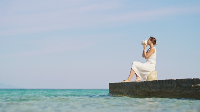 SLO MO Young woman blowing into a conch shell while sitting on a pier on the beach