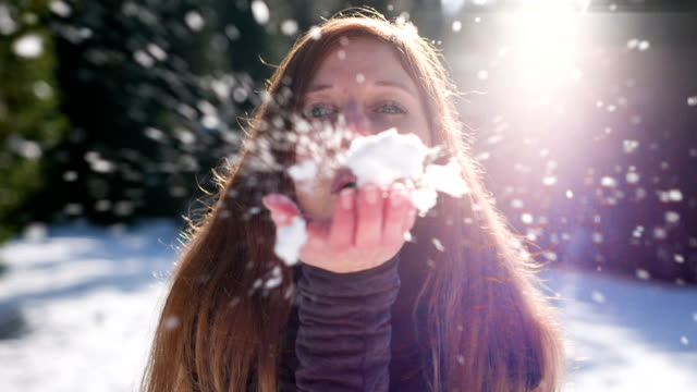 Young woman blowing snowflakes video