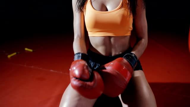 vídeos y material grabado en eventos de stock de boxer joven quita guantes de boxeo después de duro entrenamiento - artes marciales