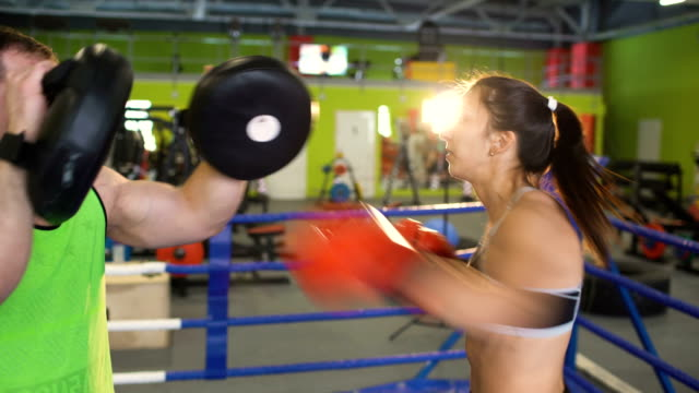 Young woman boxer training pre-match warm-up in the boxing ring with her trainer video