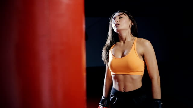 Young woman boxing punching bag in a dark hall video