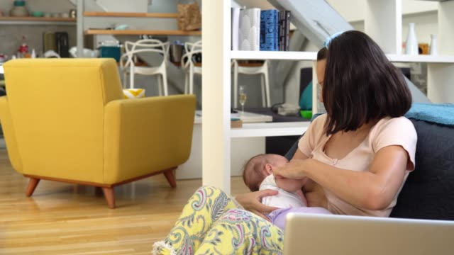 Young woman breastfeeding her baby and running the business from home